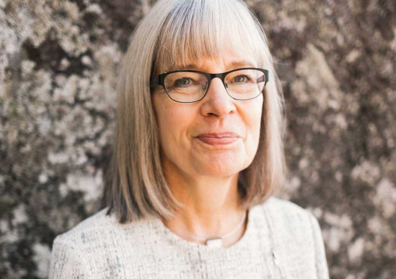 portrait of smiling woman with white hair and black glasses against rock wall
