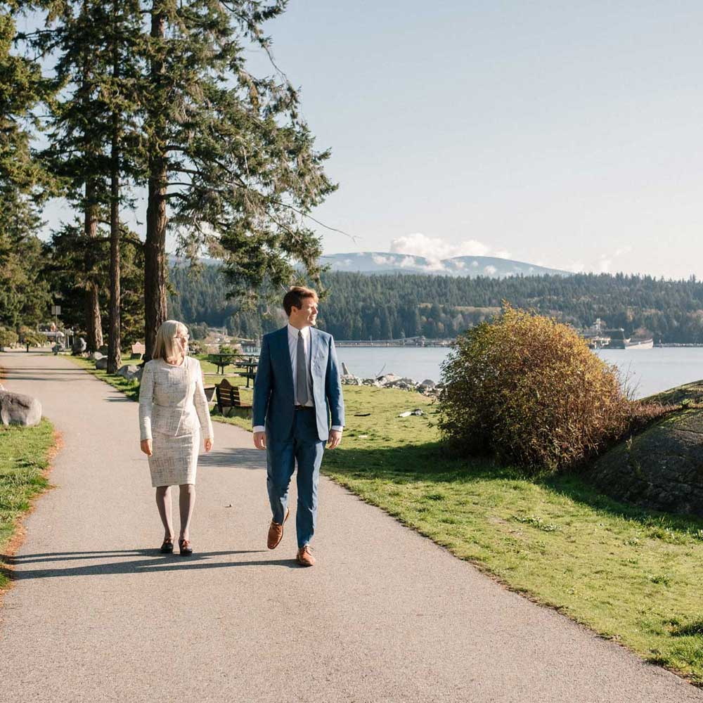 well-dressed man and woman walking along path at waterfront